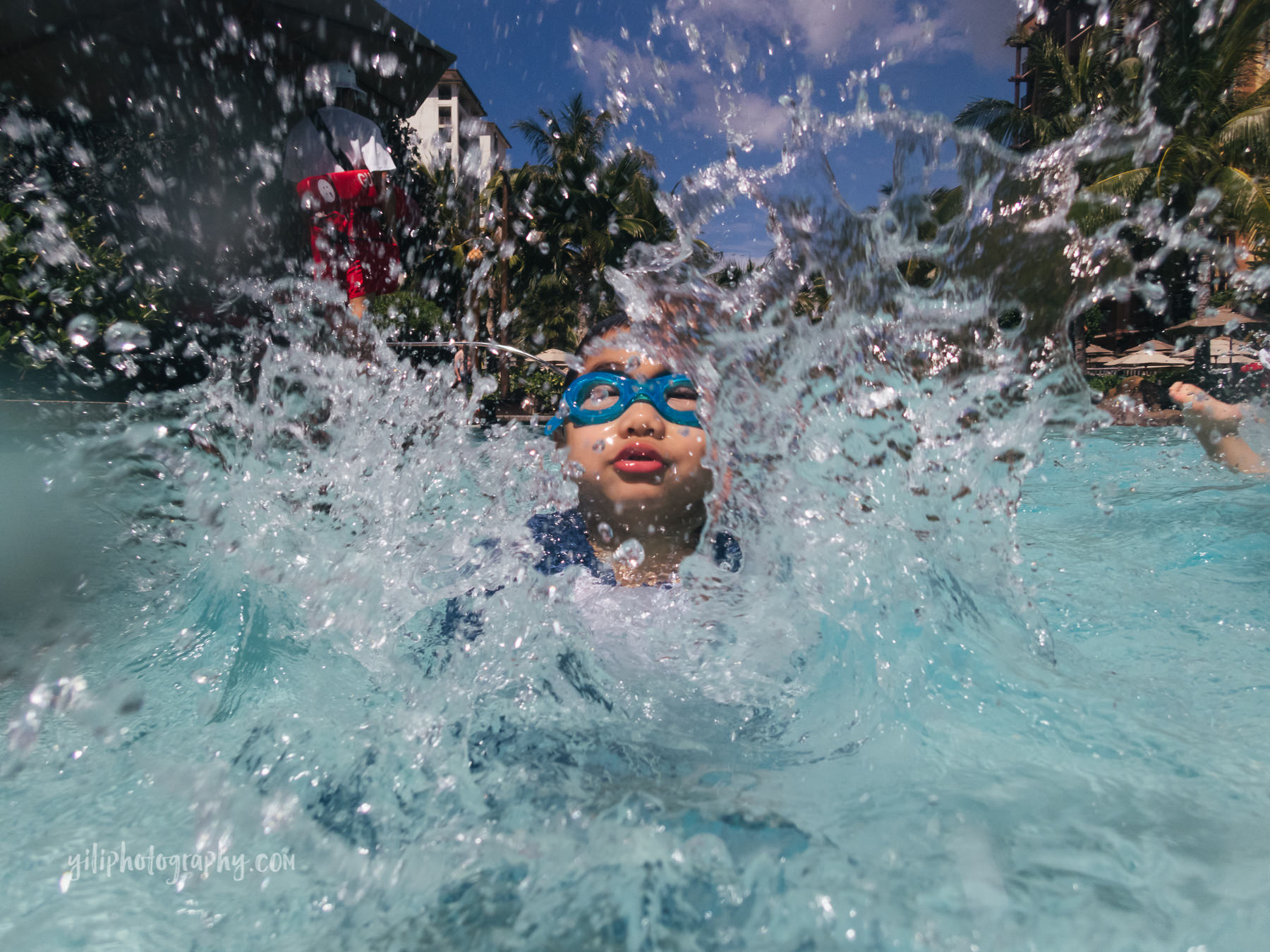 boy splashing water at camera in pool