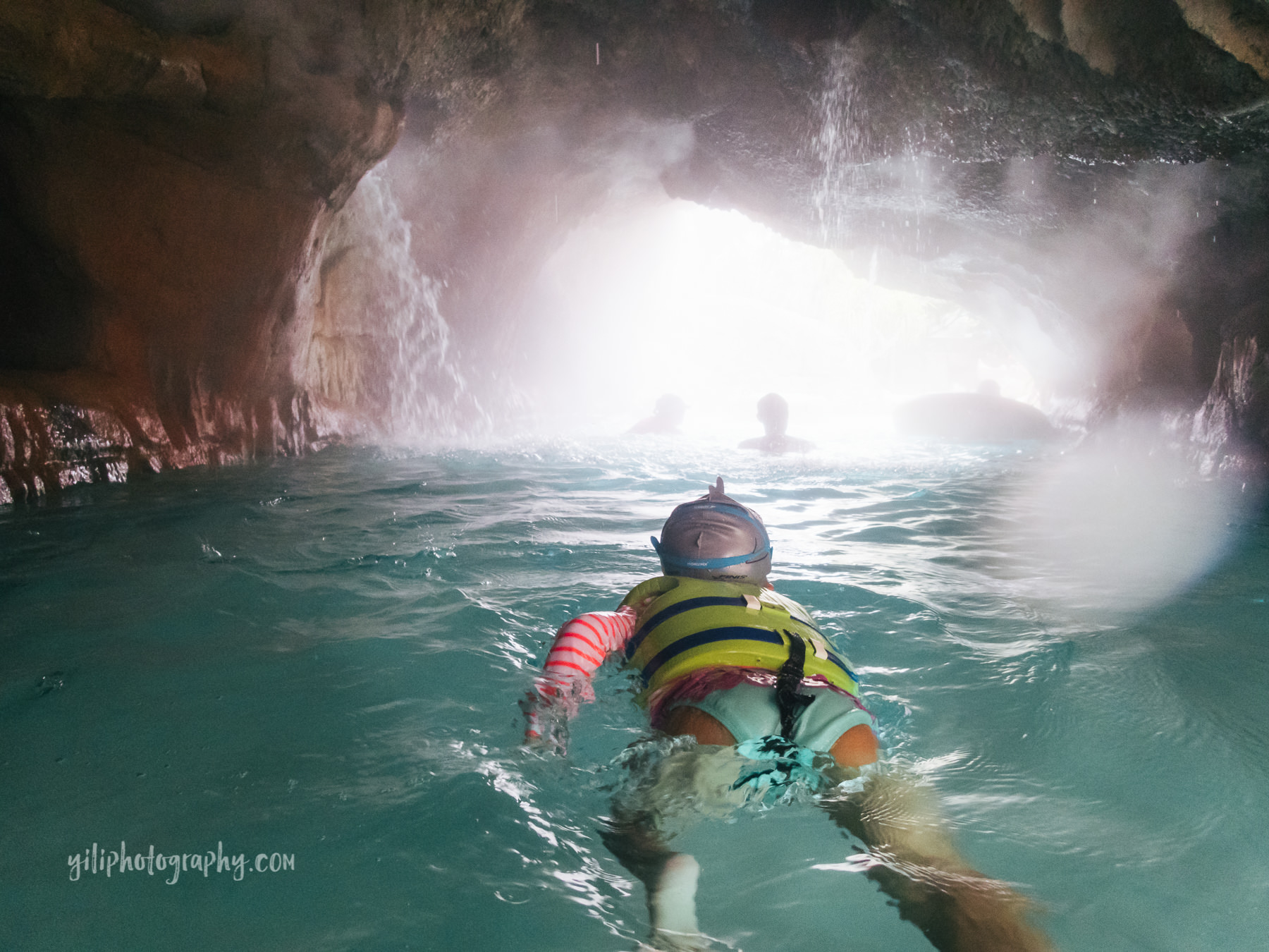 little girl swimming through lazy river cave