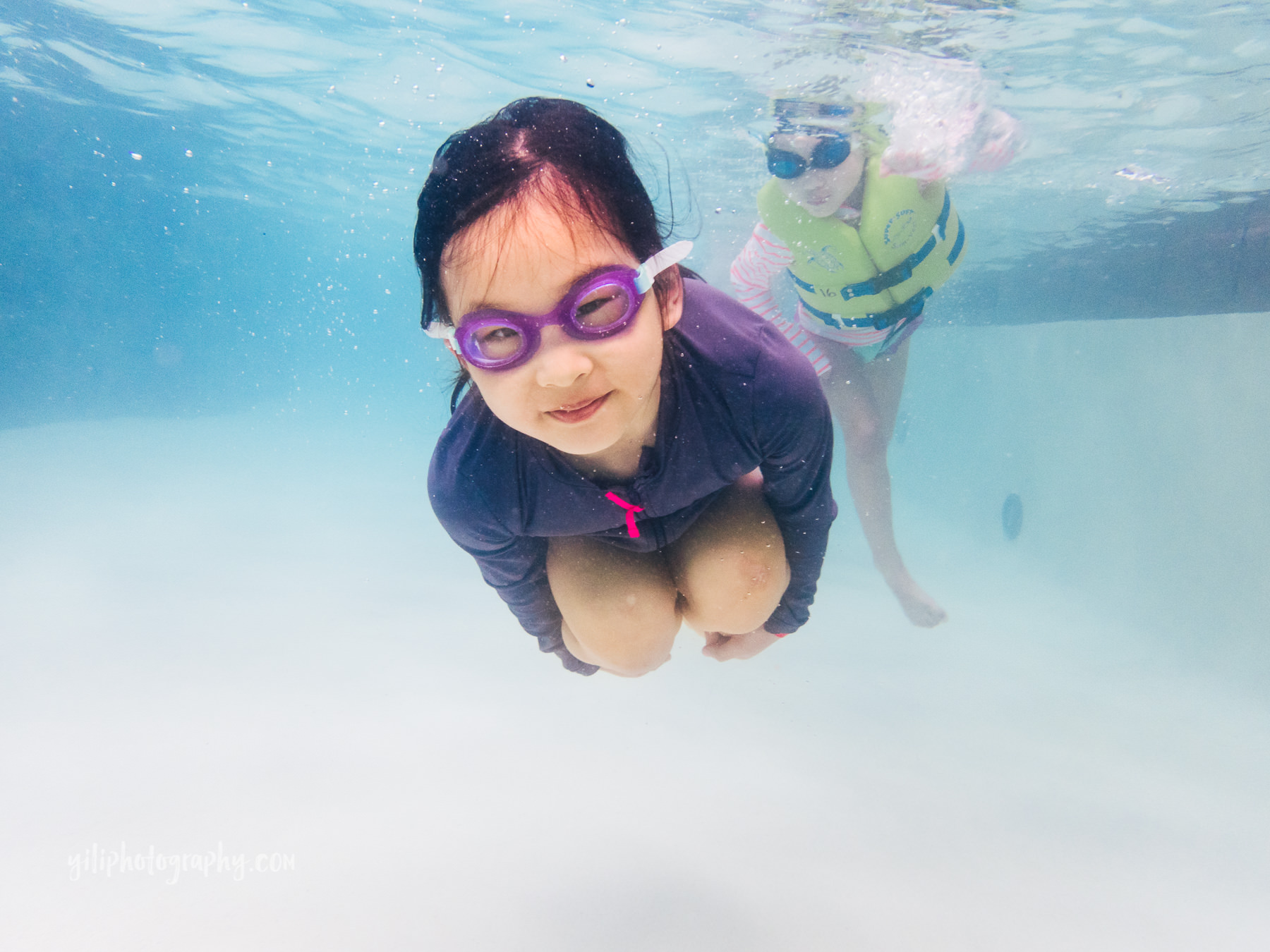 underwater photo of girl in goggles tucked in ball