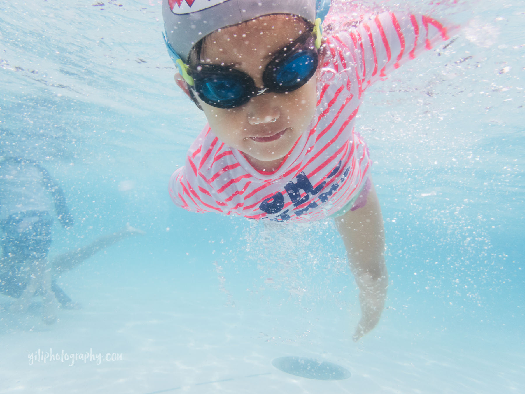 little girl in swim cap and goggles swimming underwater