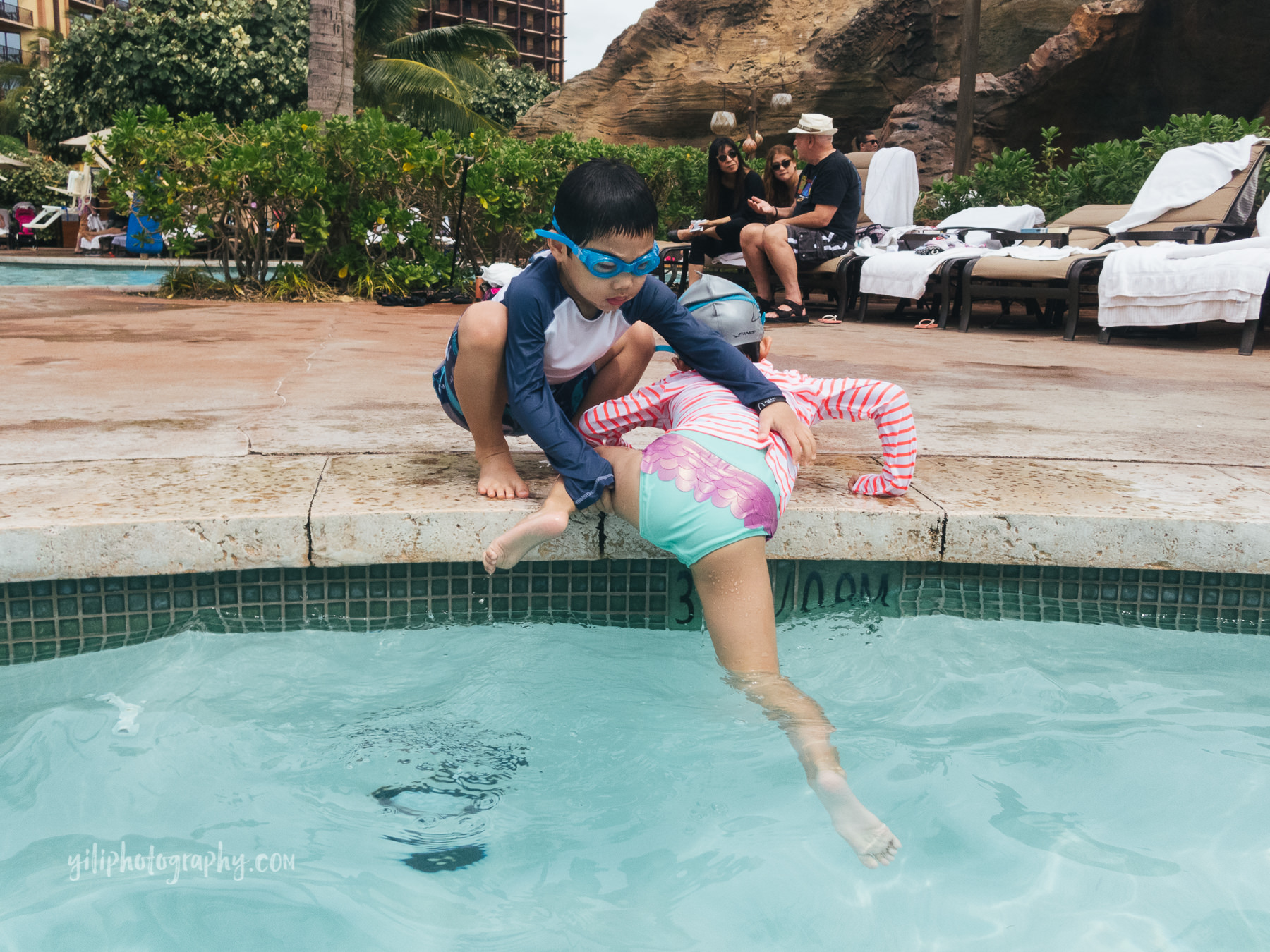 twin brother pulling sister out of pool