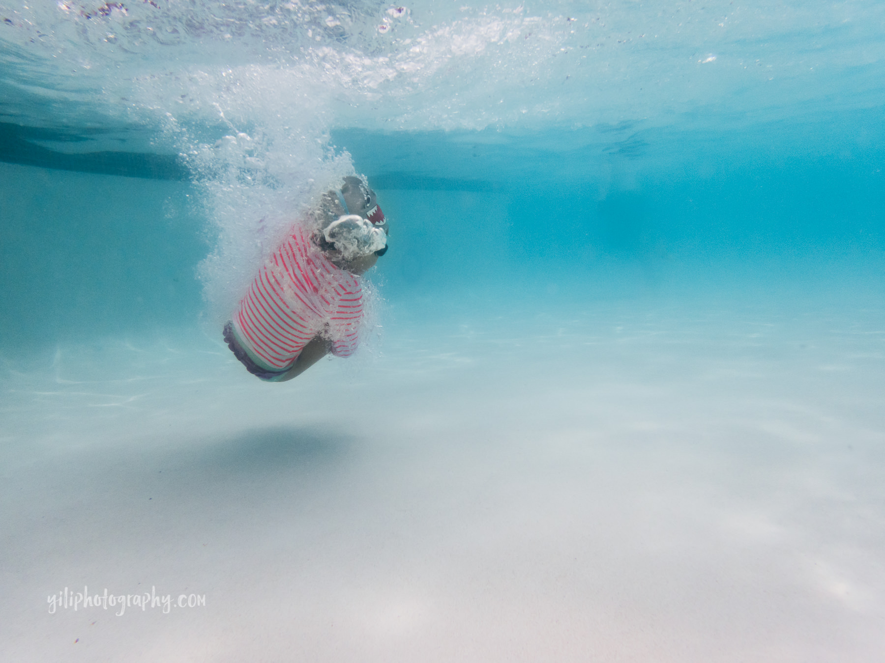 underwater photo of little girl in cannonball