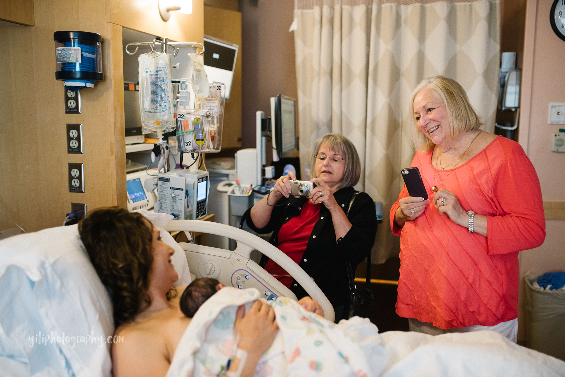 two grandmothers taking photos of their granddaughter after birth in hospital room