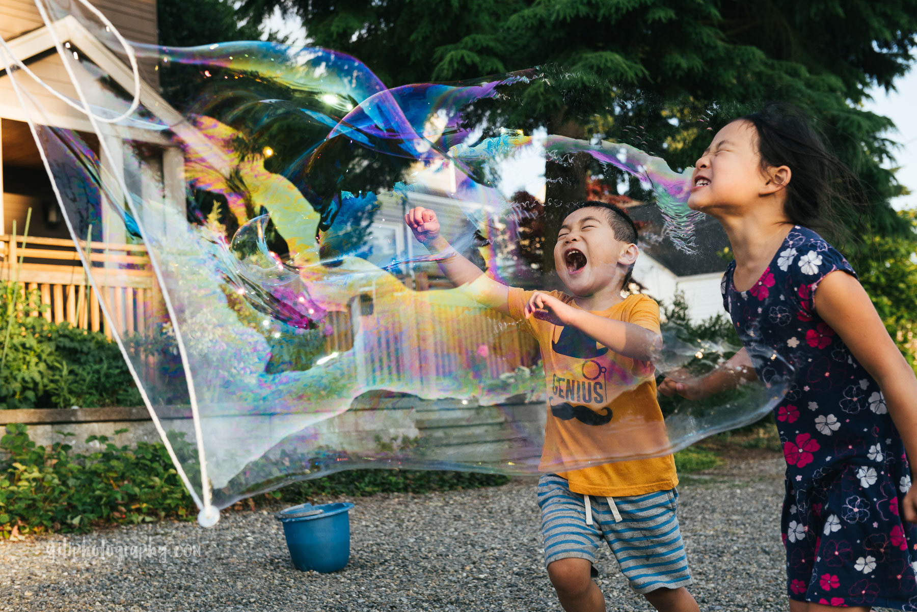 boy with big grin popping giant bubble with sister