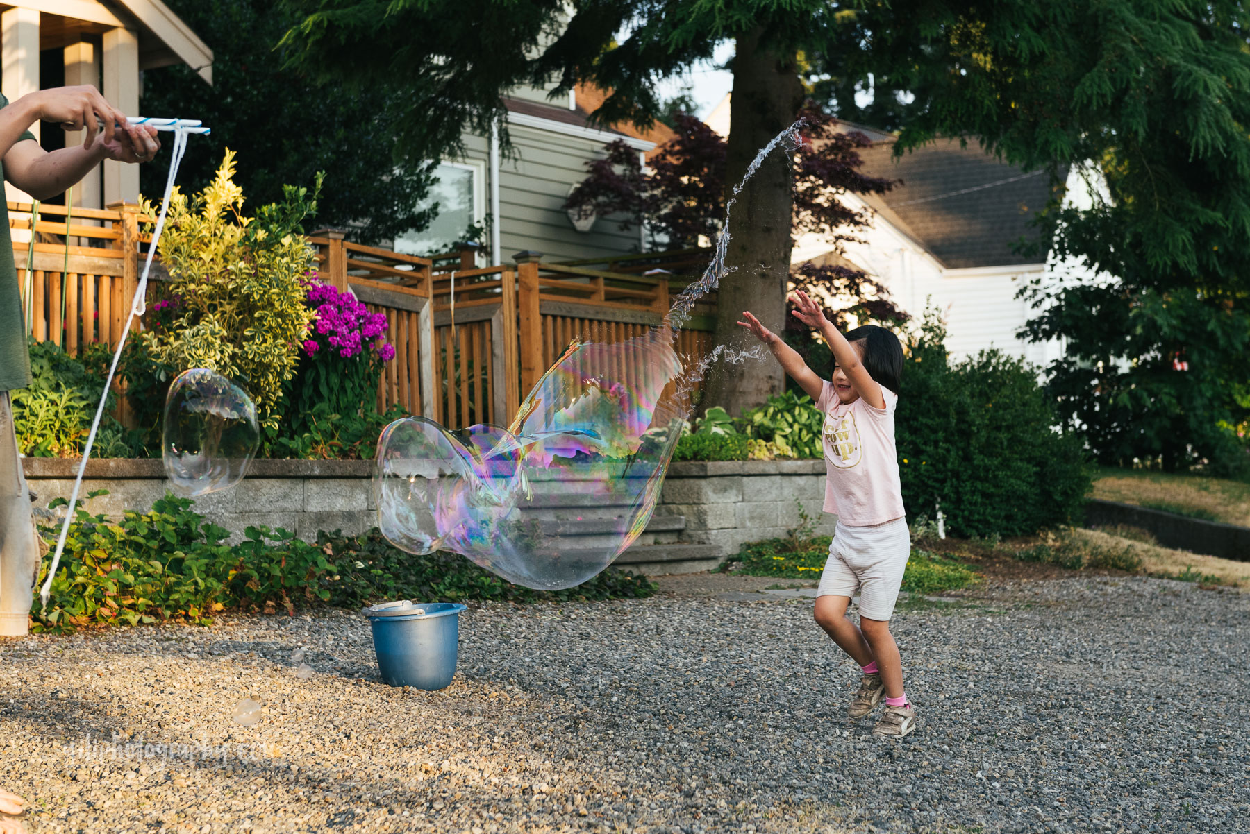 little girl with arms in air popping giant bubble