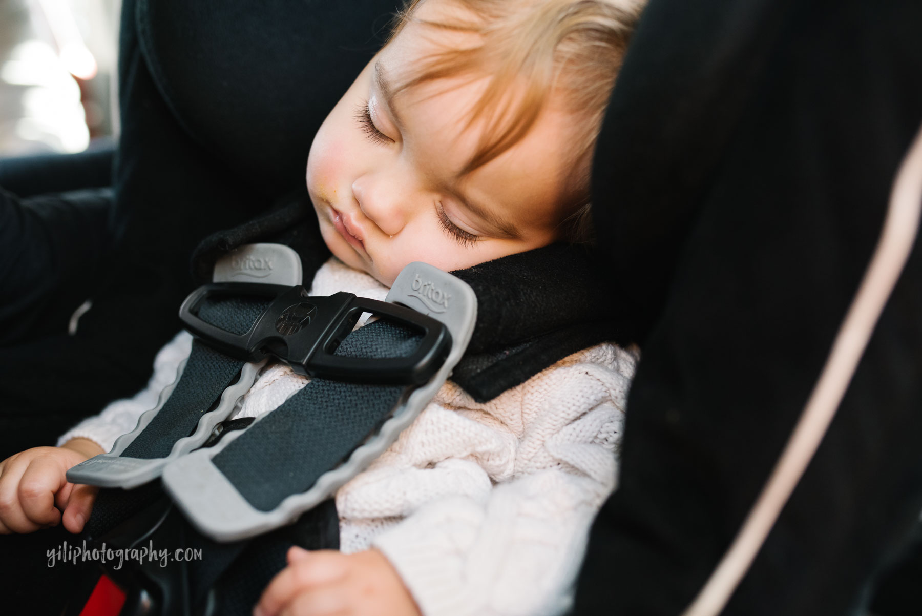 Toddler girl with long eyelashes asleep in carseat