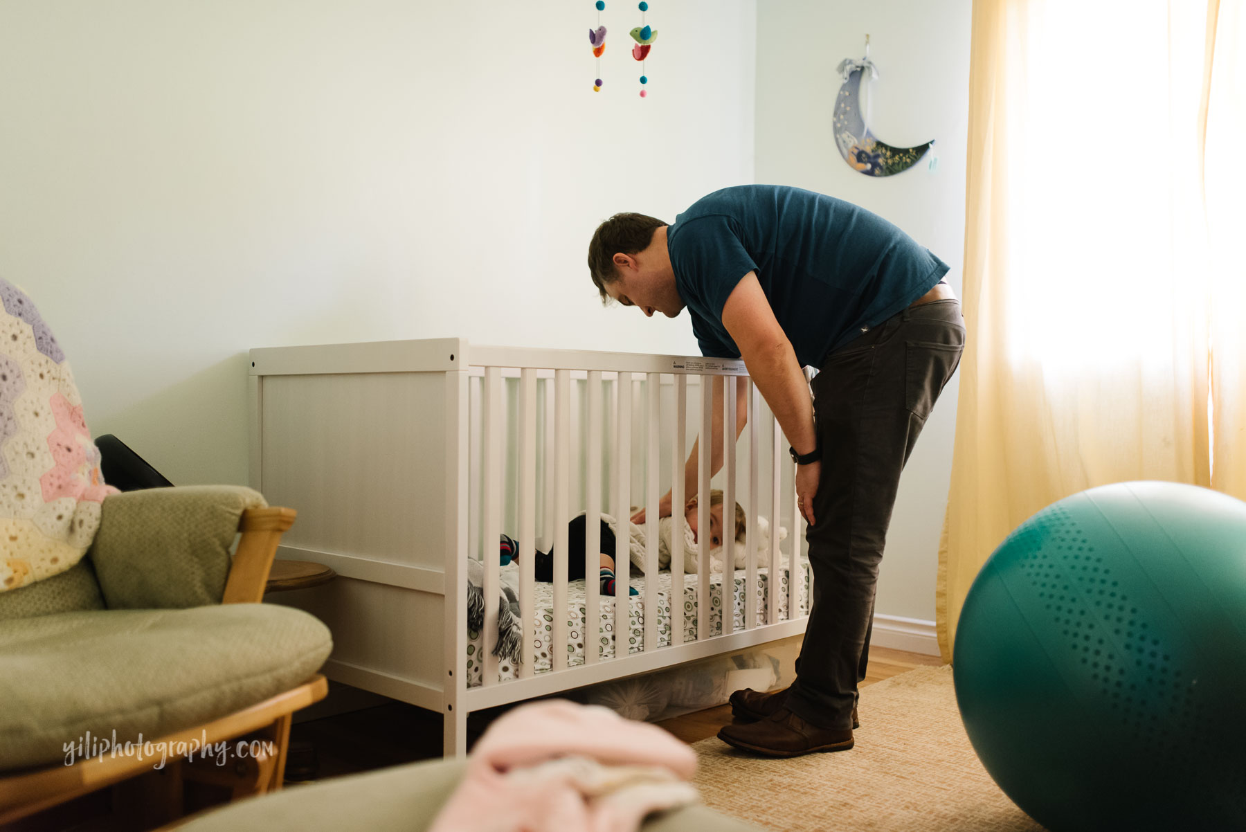 Father patting toddler girl's back in crib in nursery