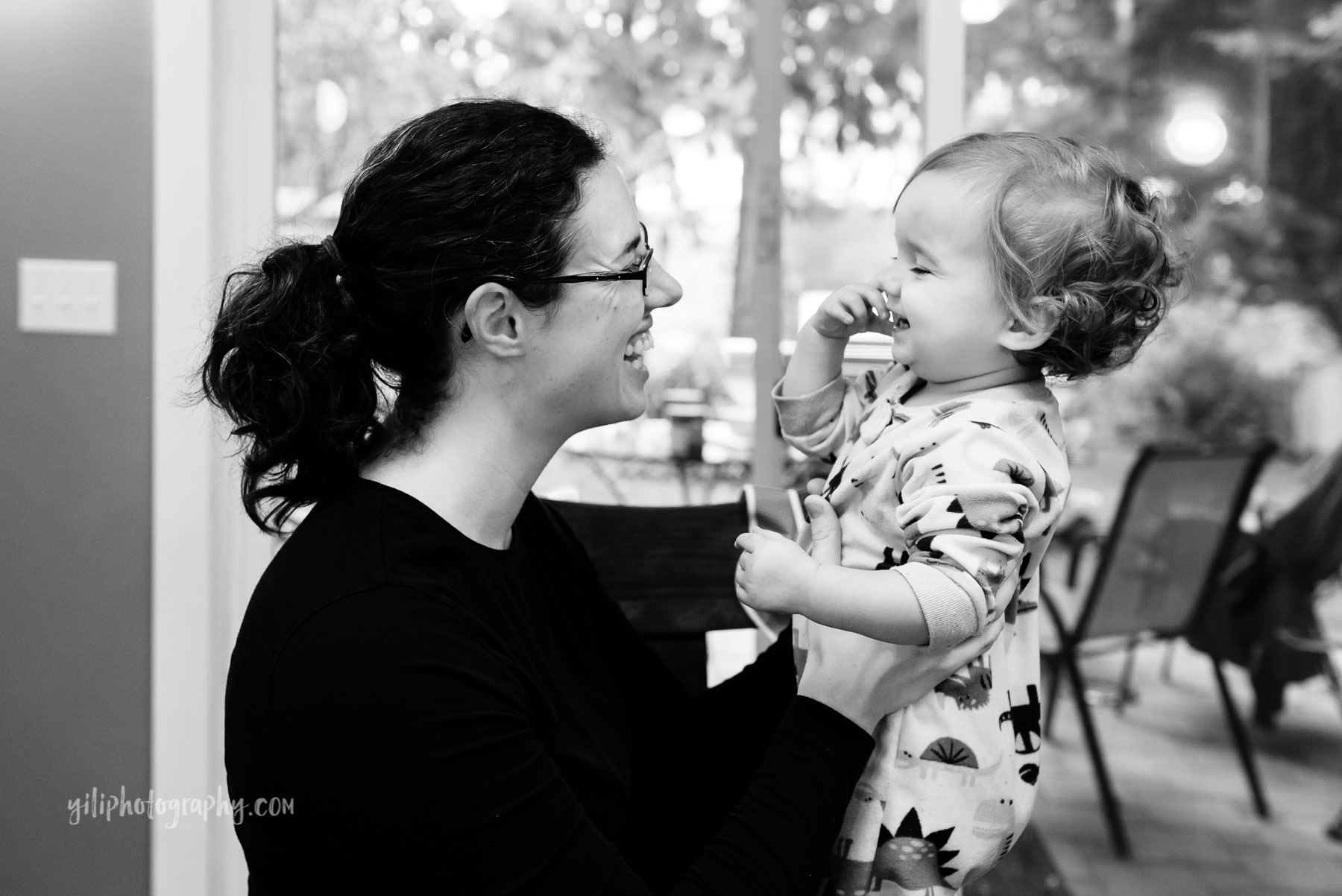 Mom smiling and laughing with toddler girl at home