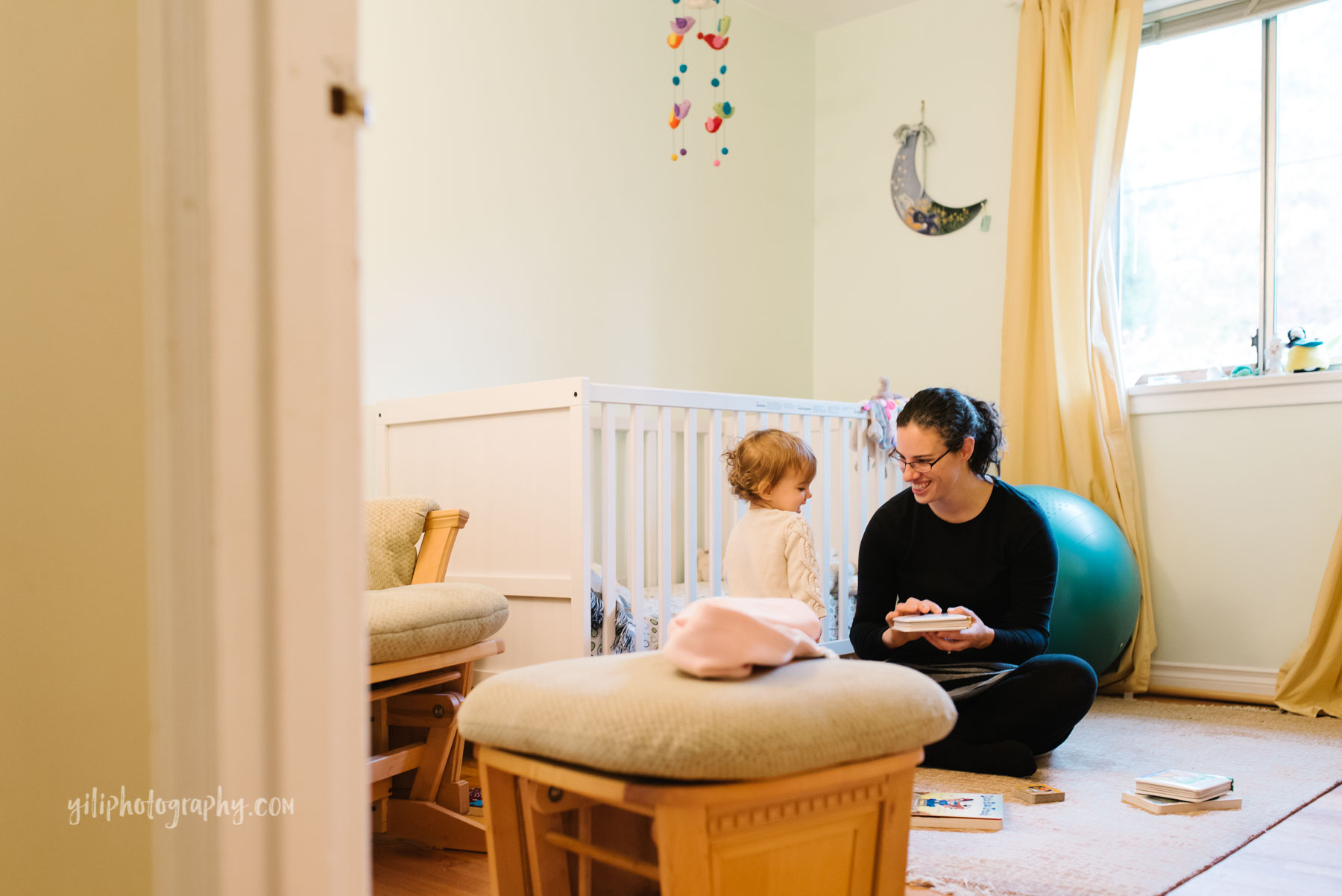 Mom reading with toddler daughter in nursery