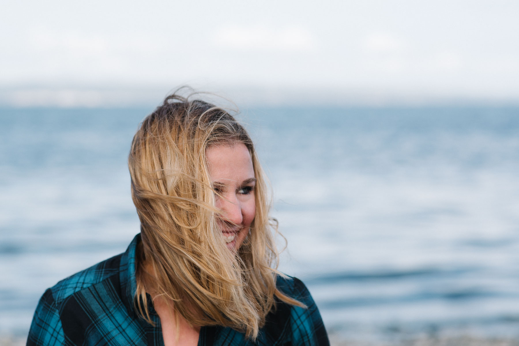 Portrait of caucasian woman with long blonde hair blowing in face at beach