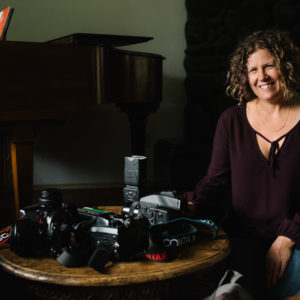 Female photographer sitting in living room with camera equipment on coffee table