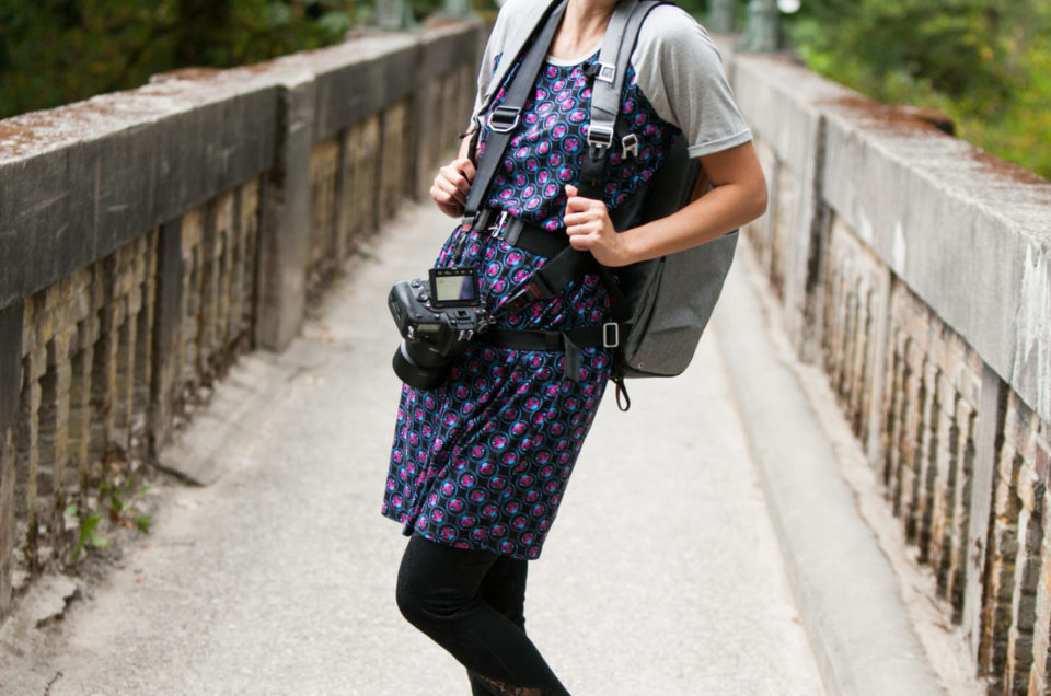 Asian female photographer posing and smiling with gear