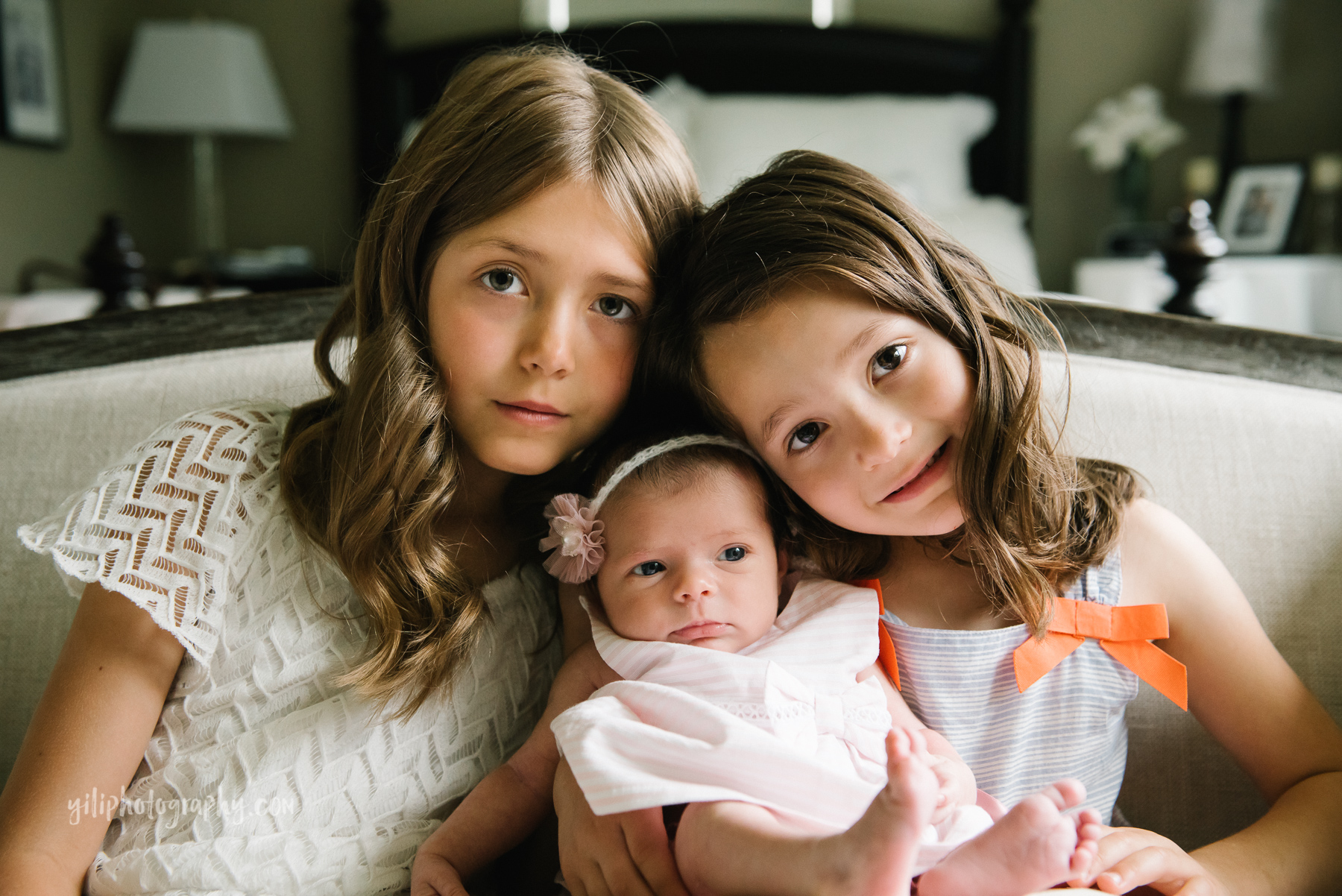 two older sisters with newborn baby sister