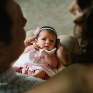 top down photo of newborn baby girl looking up at parents while they look at her