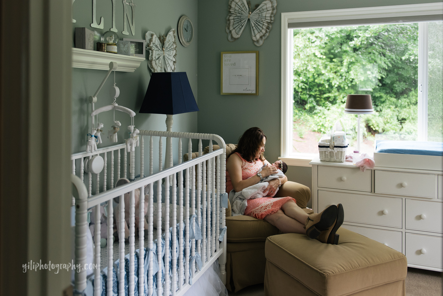 wide angle photo of mom sitting in rocker in nursery holding newborn