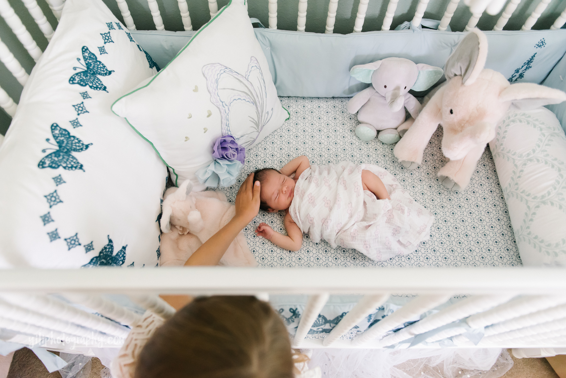 top down photo of big sister patting newborn girl's head in crib