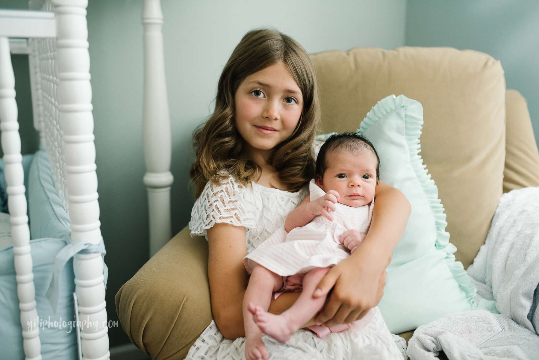 elementary school girl holding newborn baby sister in armchair