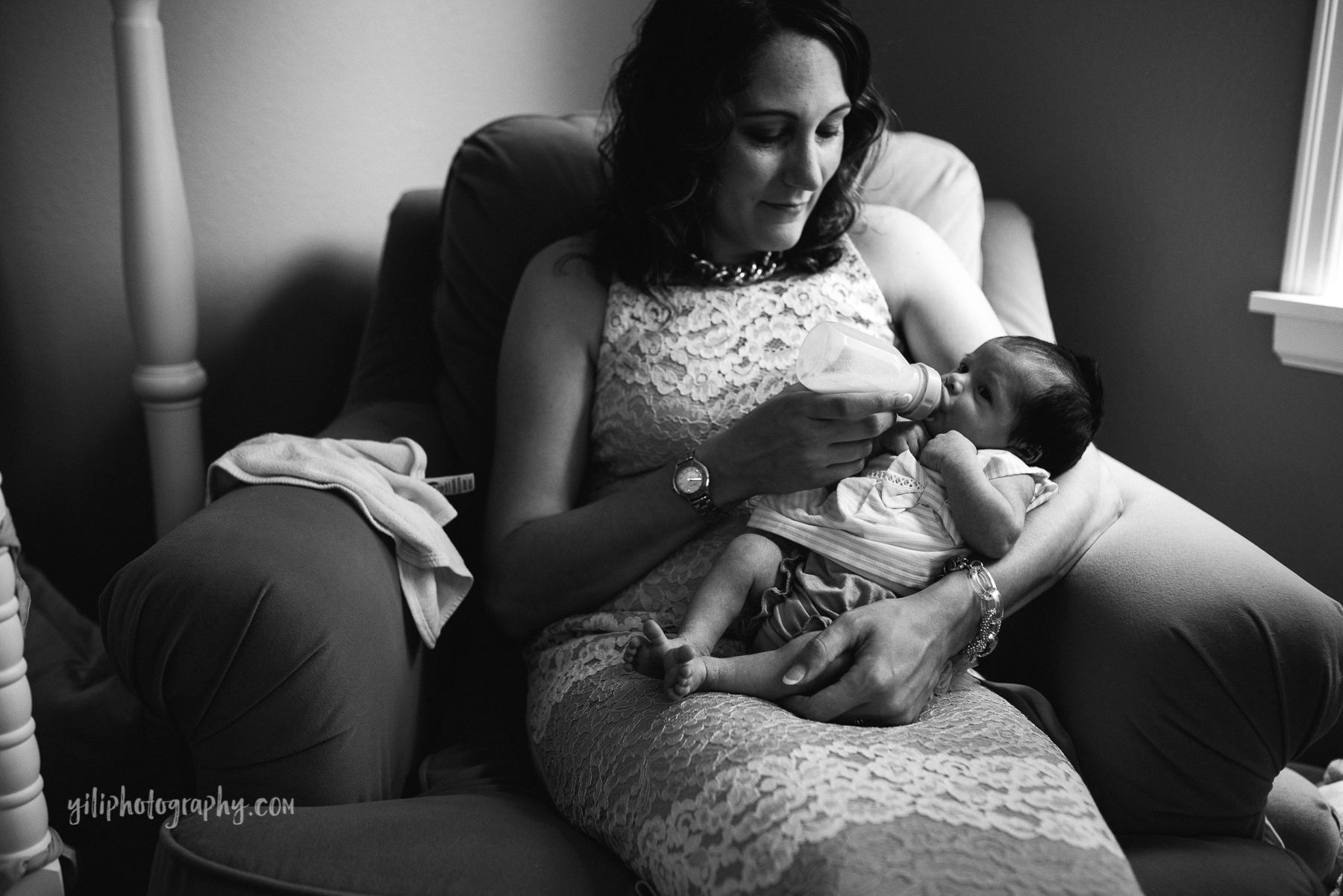 mom sitting in rocker feeding newborn baby a bottle