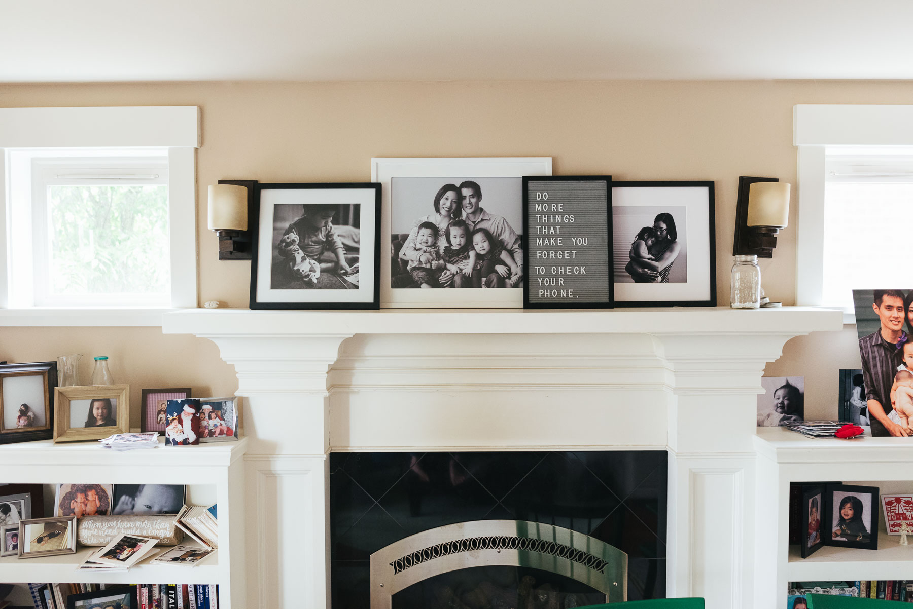 large framed photographs above fireplace mantle in home