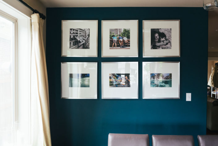 large square framed photographs in wall gallery on blue dining room wall