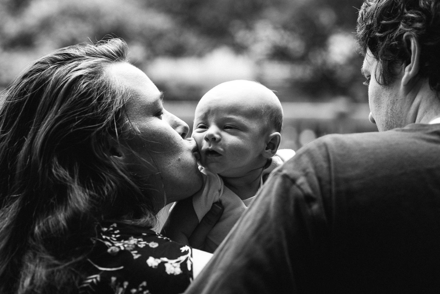 black and white photo of mom kissing newborn baby over dad's shoulder