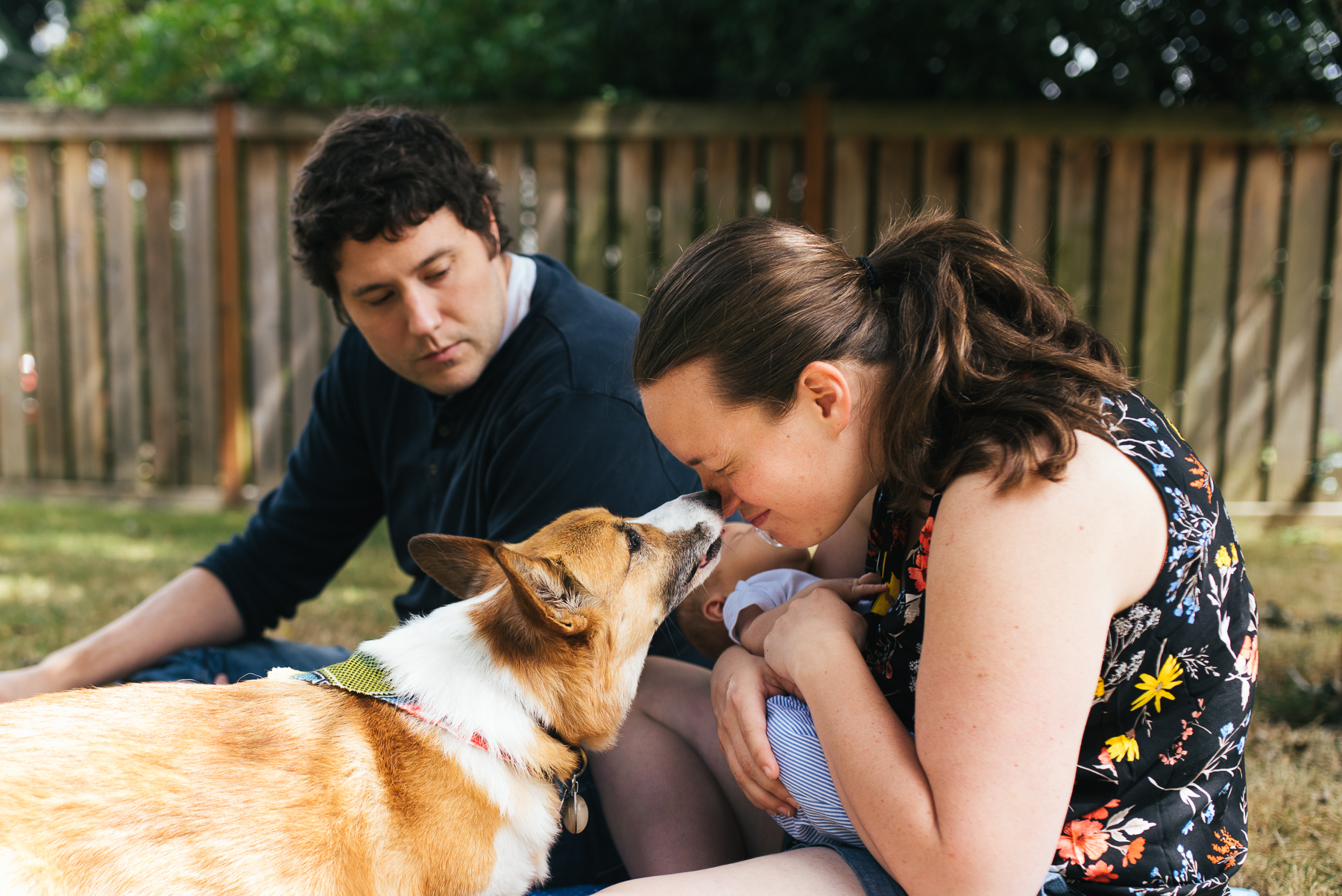 woman giving dog a kiss while sitting in yard with husband