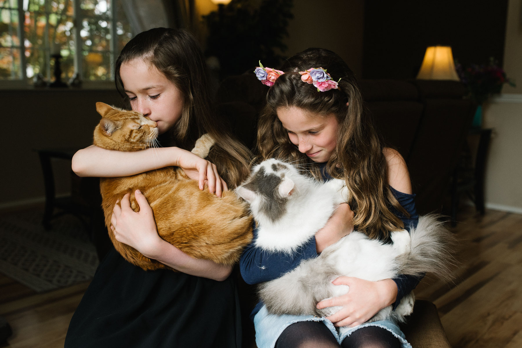 two elementary aged girls cuddle with their two cats