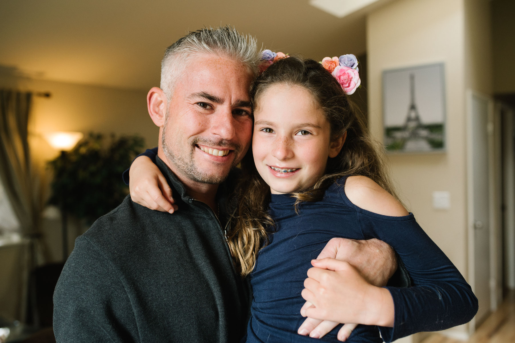 Dad with elementary aged daughter hugging in living room