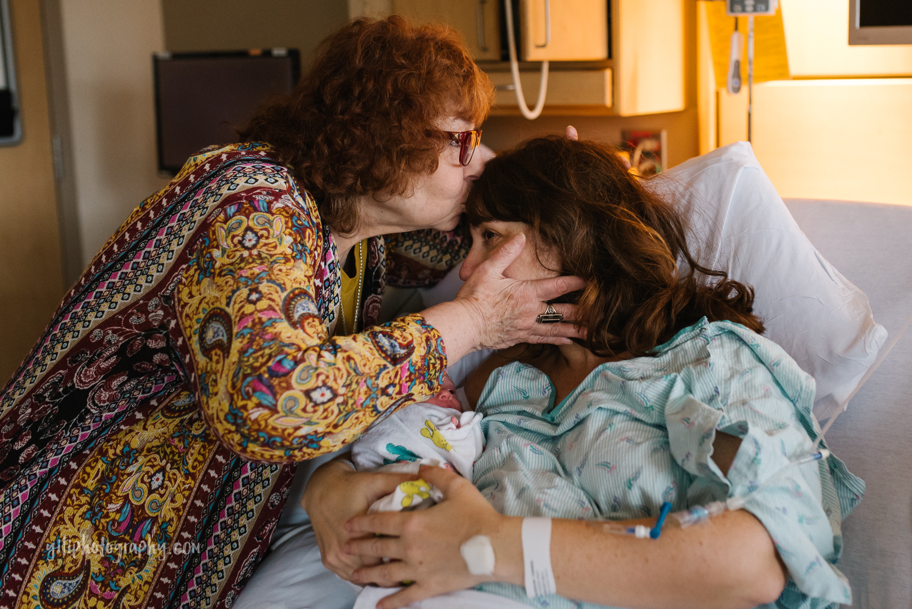 grandmother kisses her daughter who just gave birth