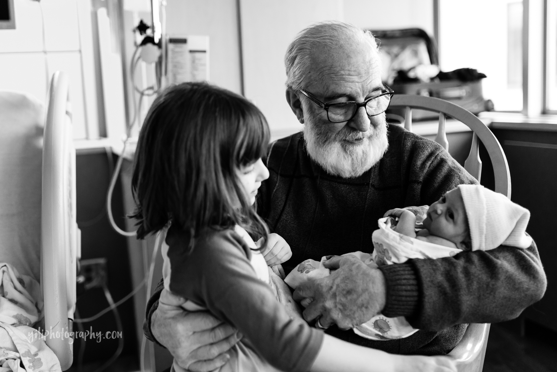 grandfather holds newborn baby in hospital rocker while hugging older granddaughter