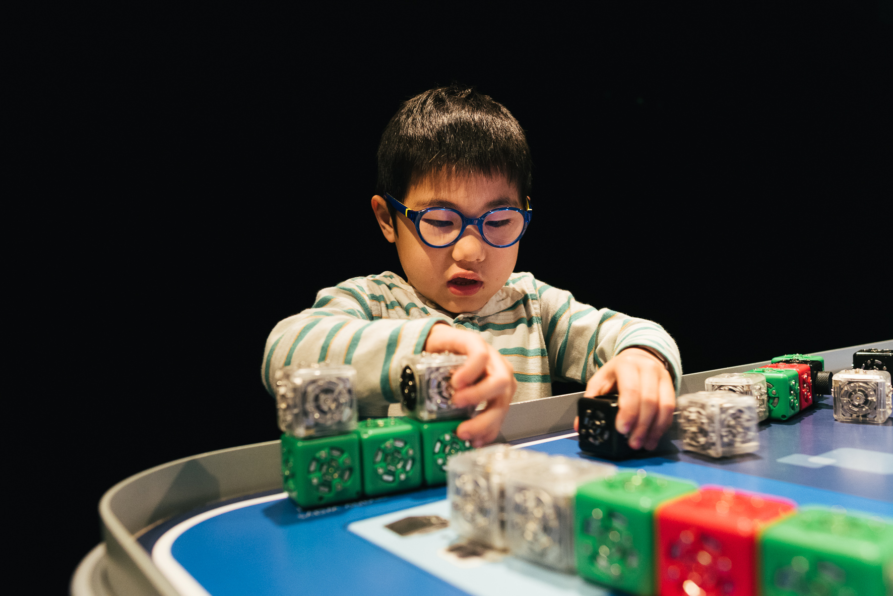 little asian boy configuring robot parts