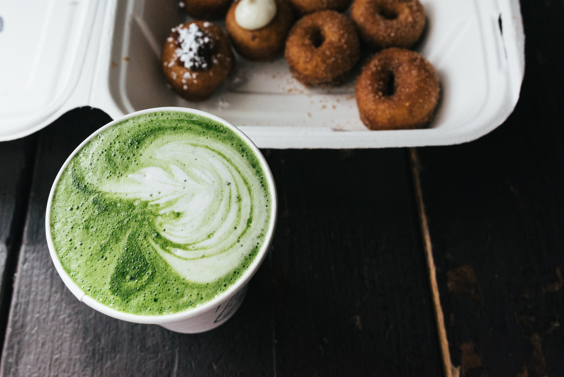 matcha green tea latte with doughnuts in background