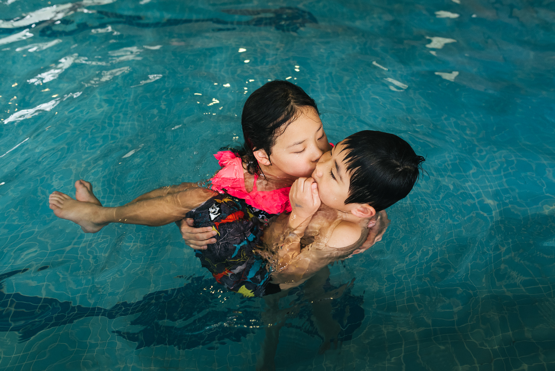 big sister cuddling with little brother in pool