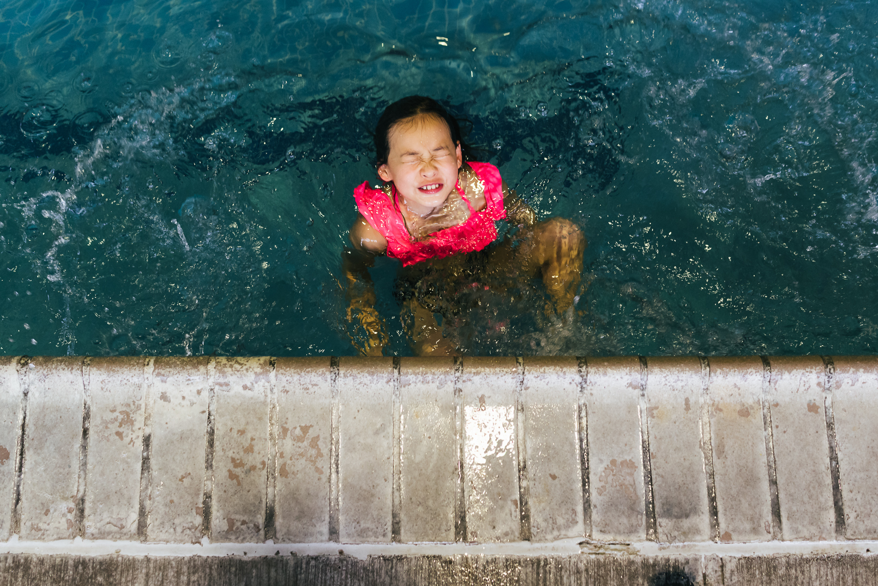 girl with silly face in pool