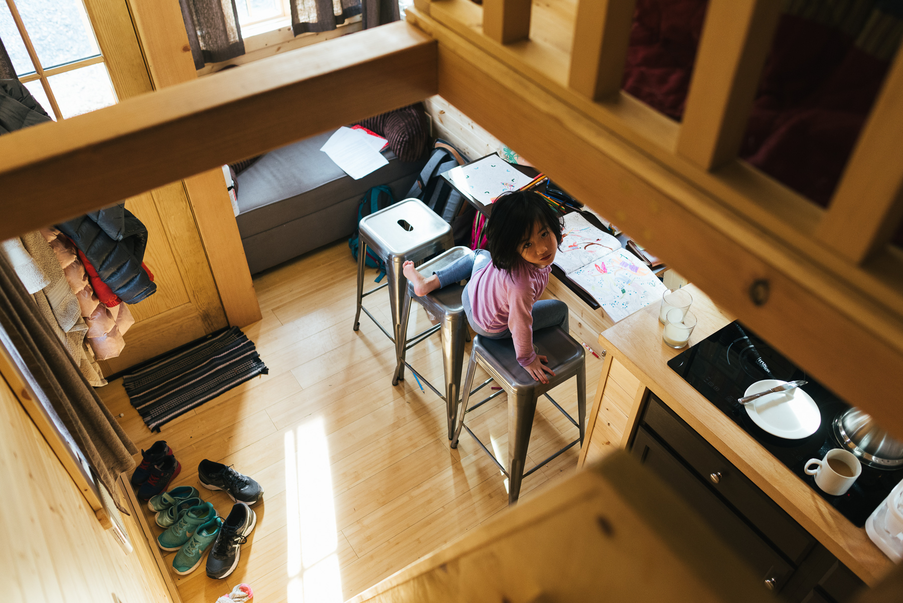 photo from loft of little girl in downstairs of tiny home