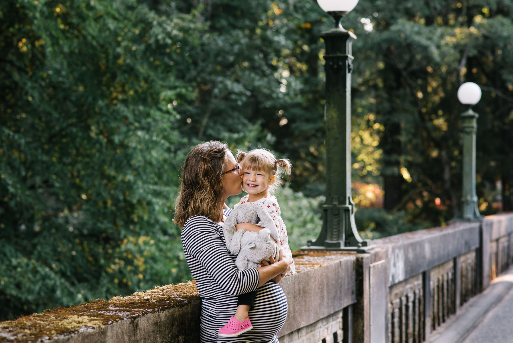 pregnant mother kissing two year old on cheek on footbridge in washington park arboretum