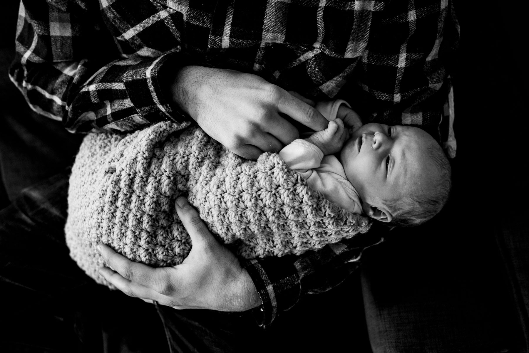 close up of dad holding newborn baby