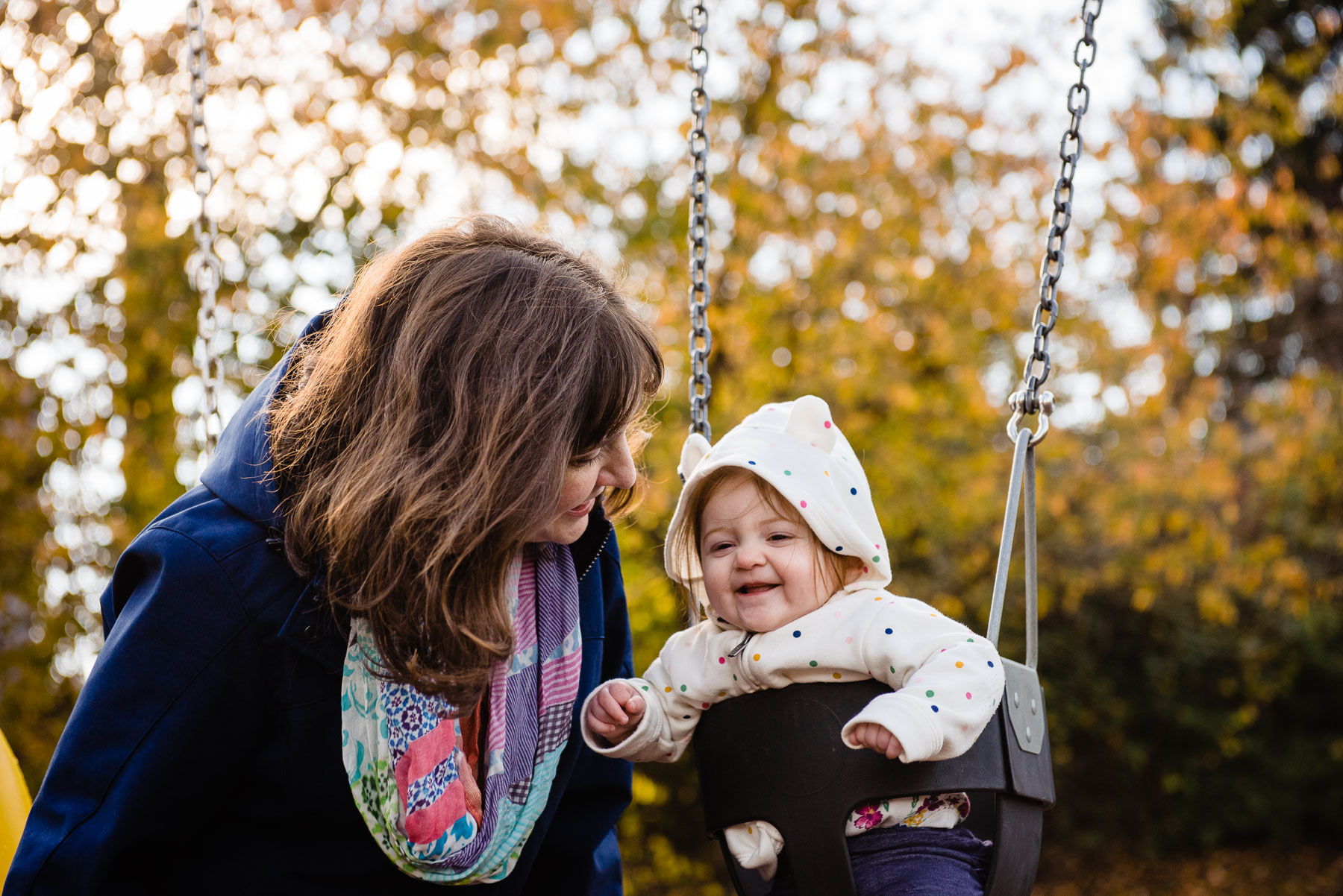 mom talking to baby on swing at playground