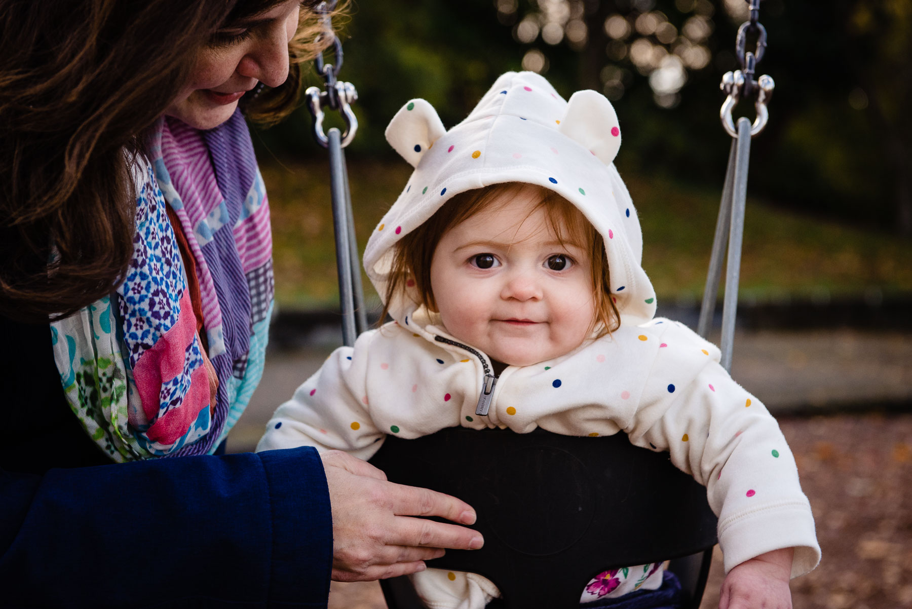 baby with hoodie on swing