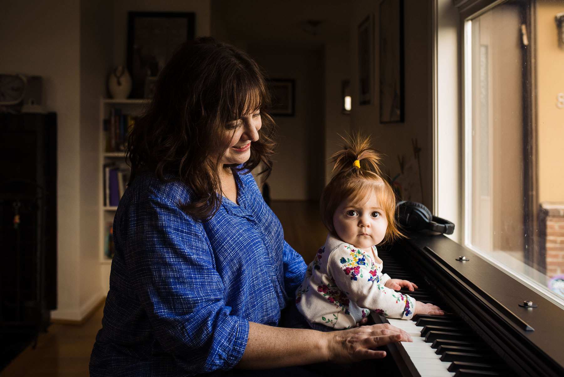 mother sitting at piano with baby
