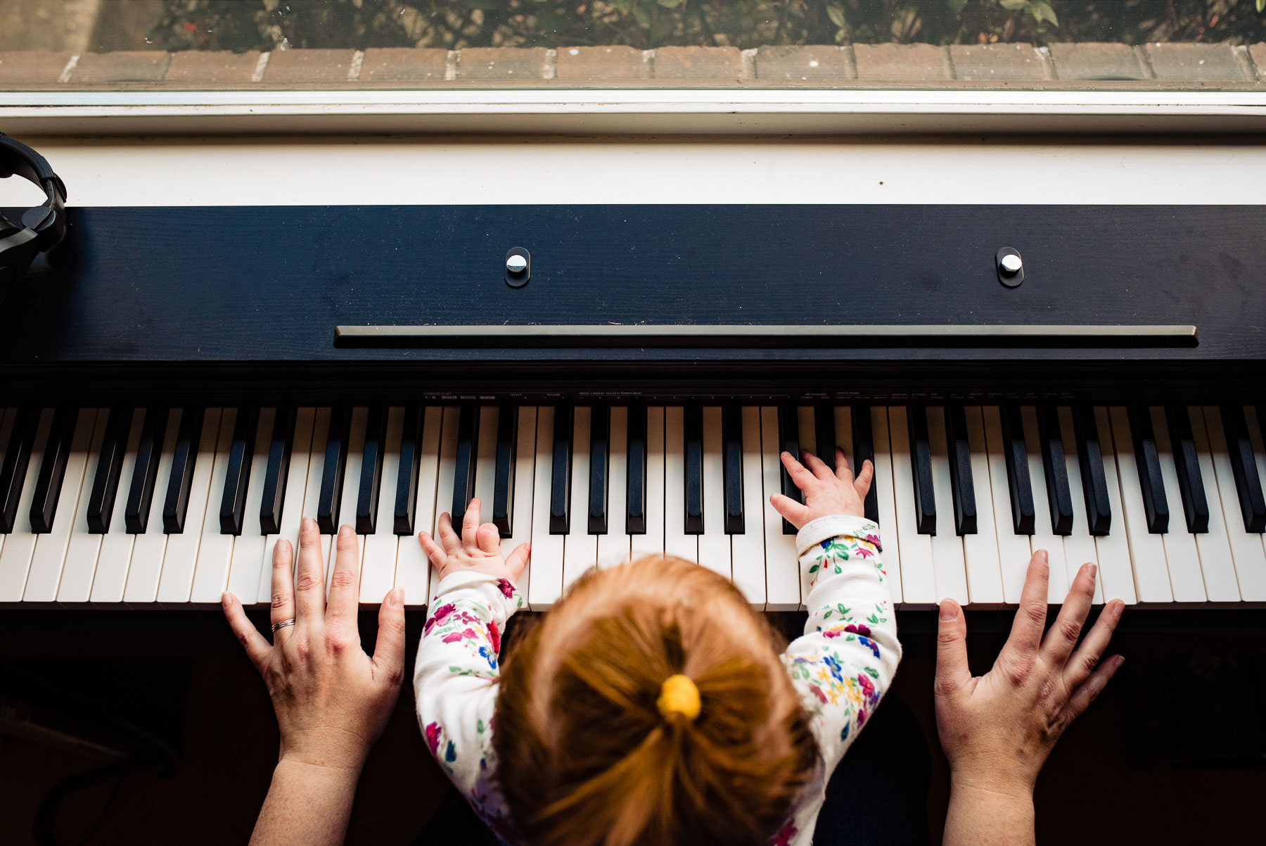 top down photo of mom playing piano with baby