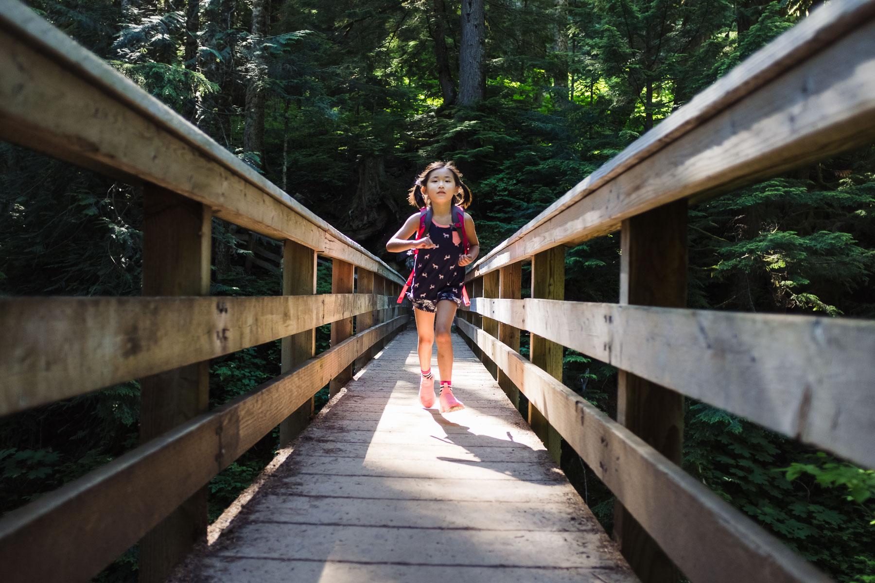 Little Asian girl crossing bridge on Denny Creek trail hike