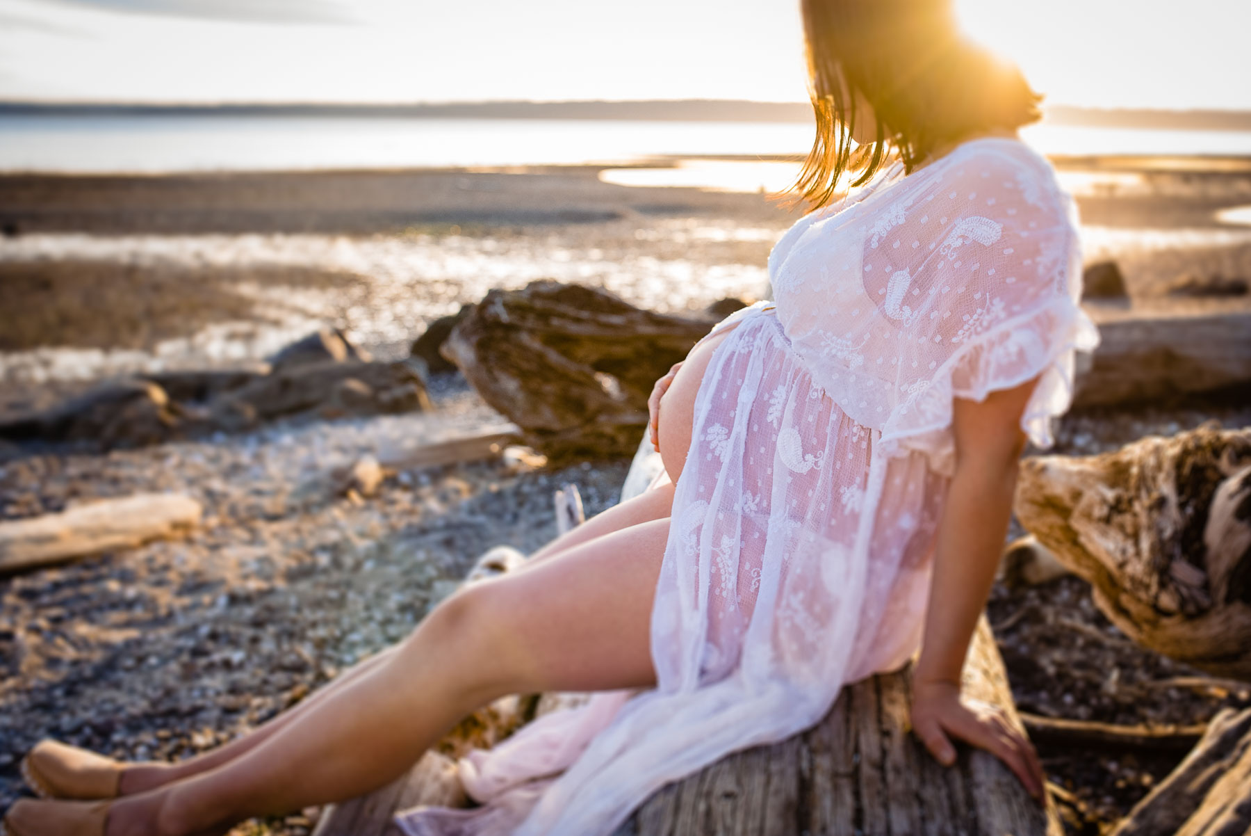 pregnant woman at beach sitting on driftwood log