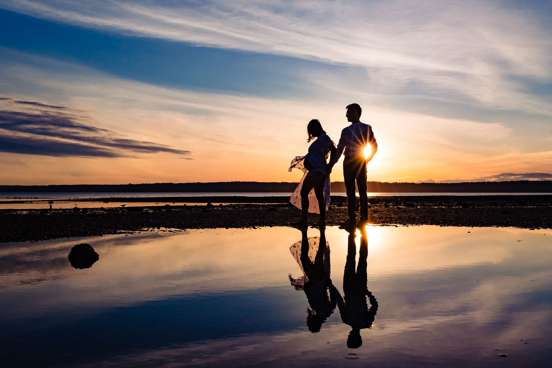 sunset silhouette of expecting couple at beach with reflection in water