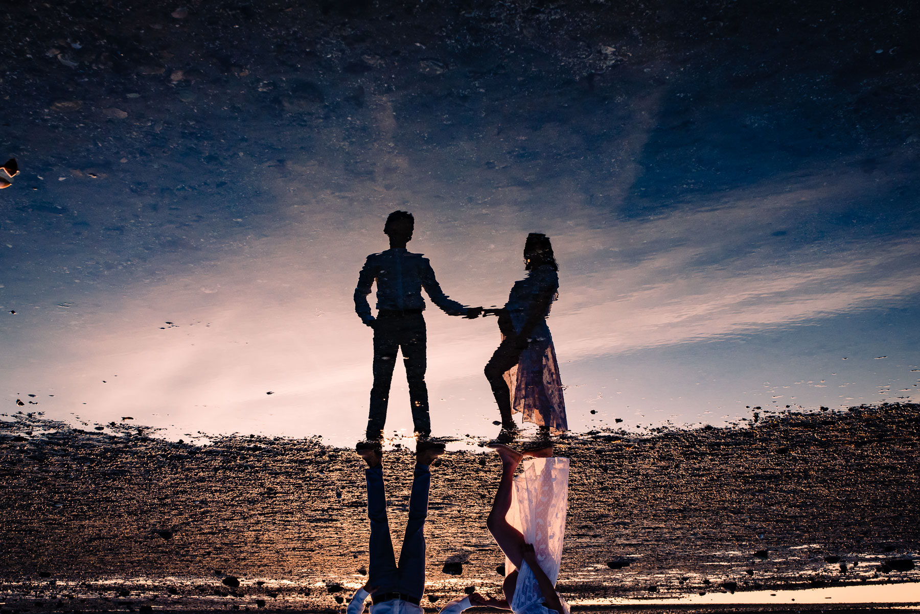 reflection of pregnant couple in water