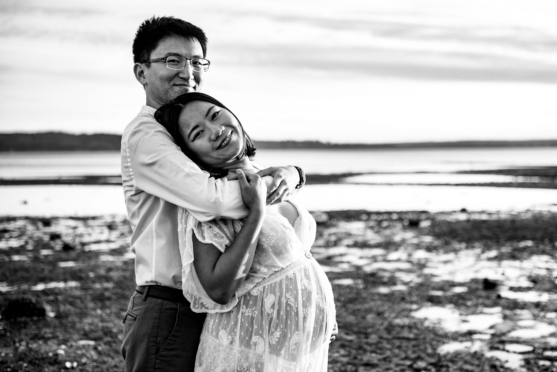 black and white photo of Asian expectant couple at beach