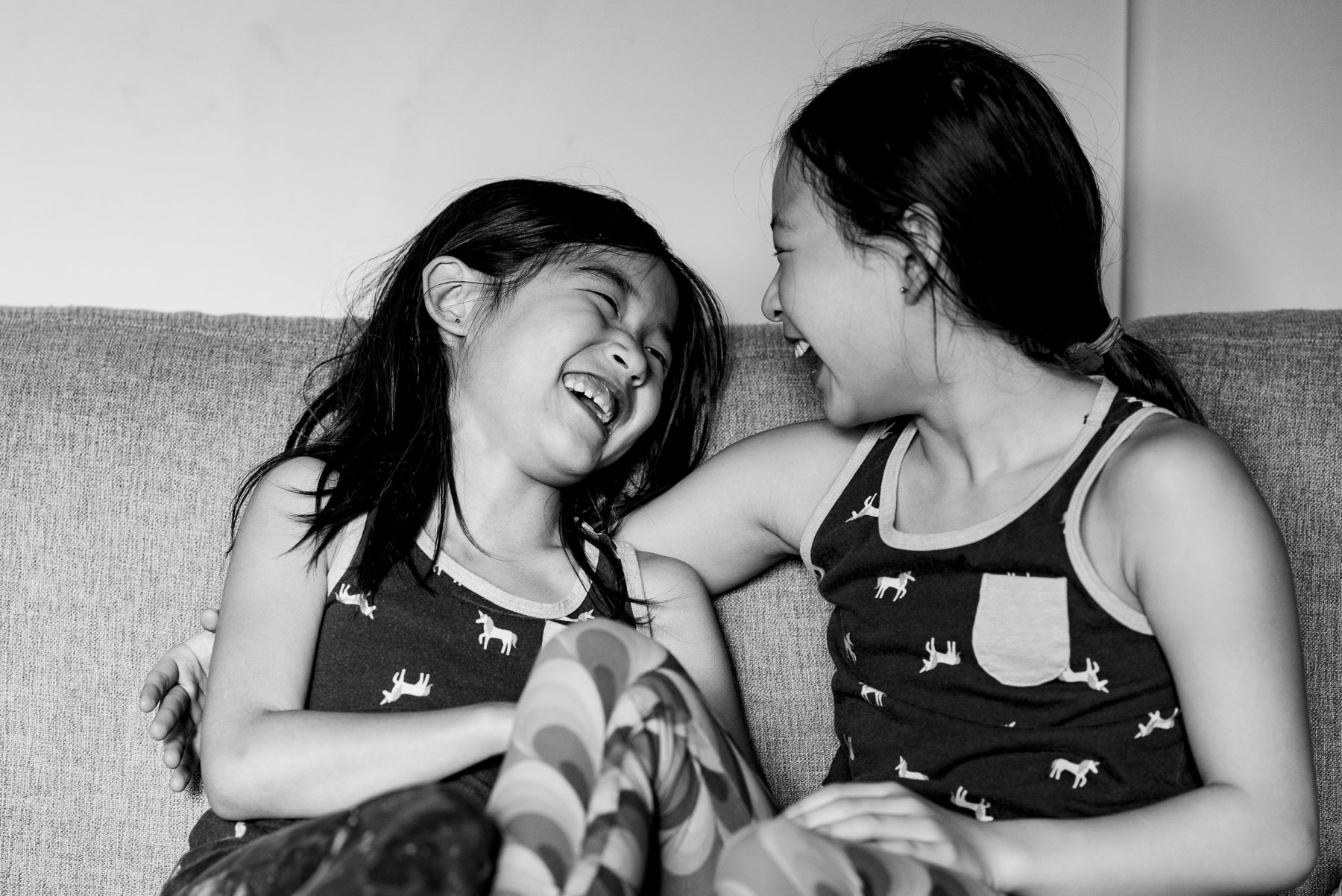 Asian sisters laughing together at home