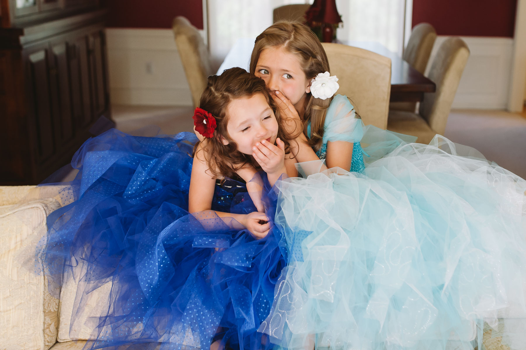two girls dressed up in Frozen dresses whispering to each other
