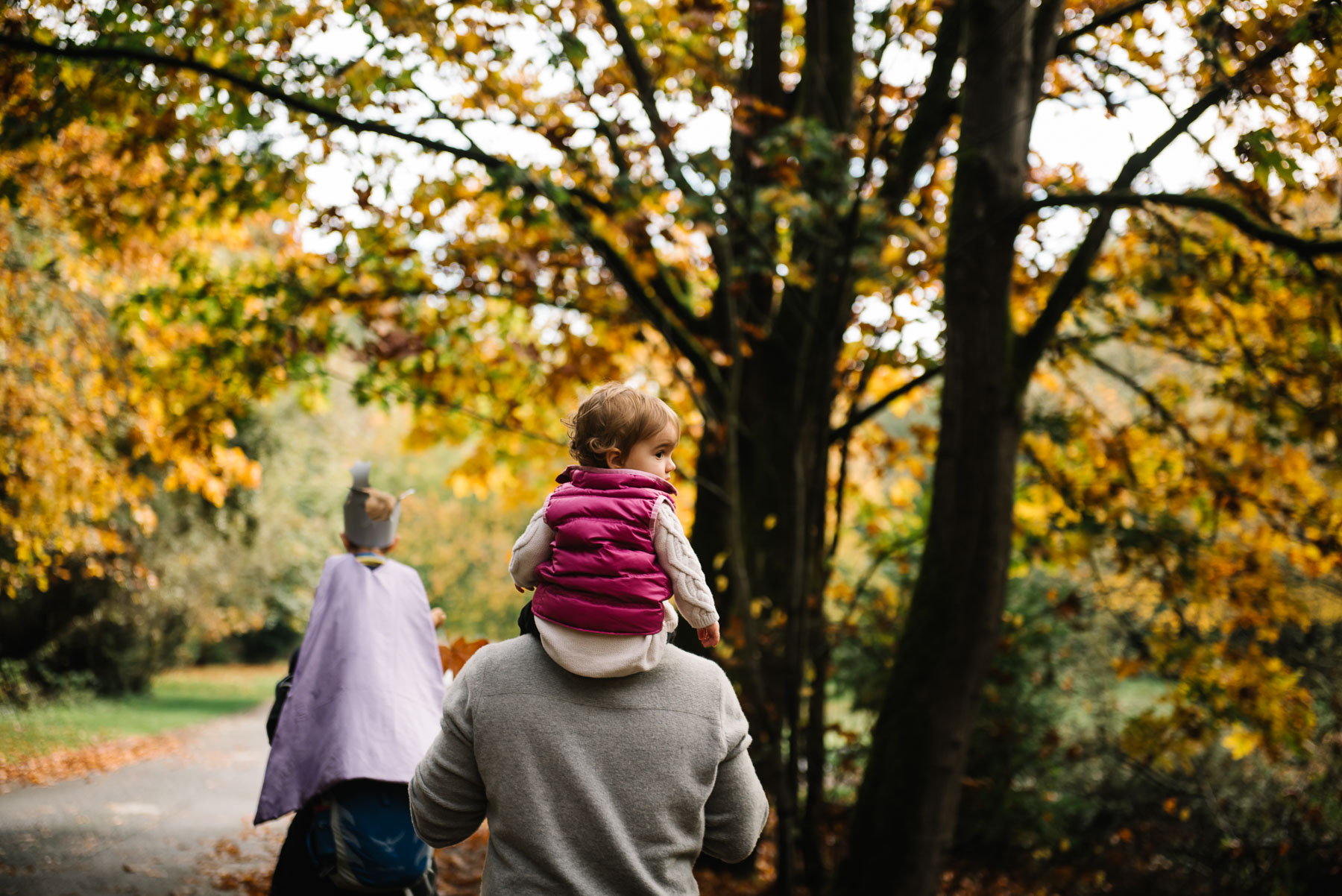 2 kids riding on top parents shoulders among fall leaves